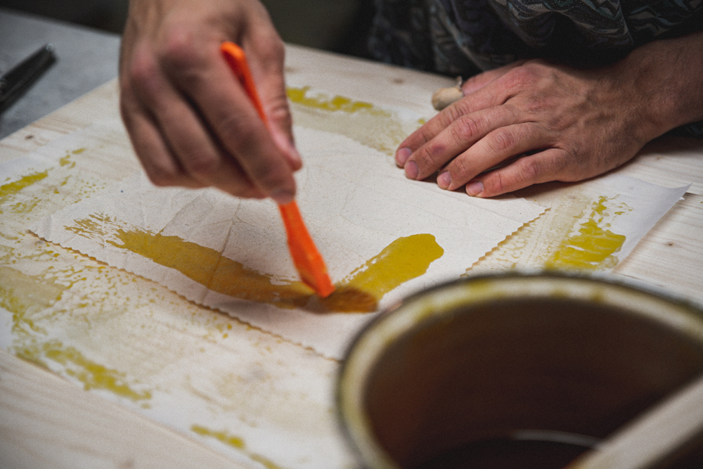 Bienenwachstuch Workshop mit Lukas Max Baumann in der Guten Stube Andeslbuch. Das Bienenwachs wird mit dem Pinsel auf Baumwollstoff aufgetragen. Foto von Stanglechner Thomas.