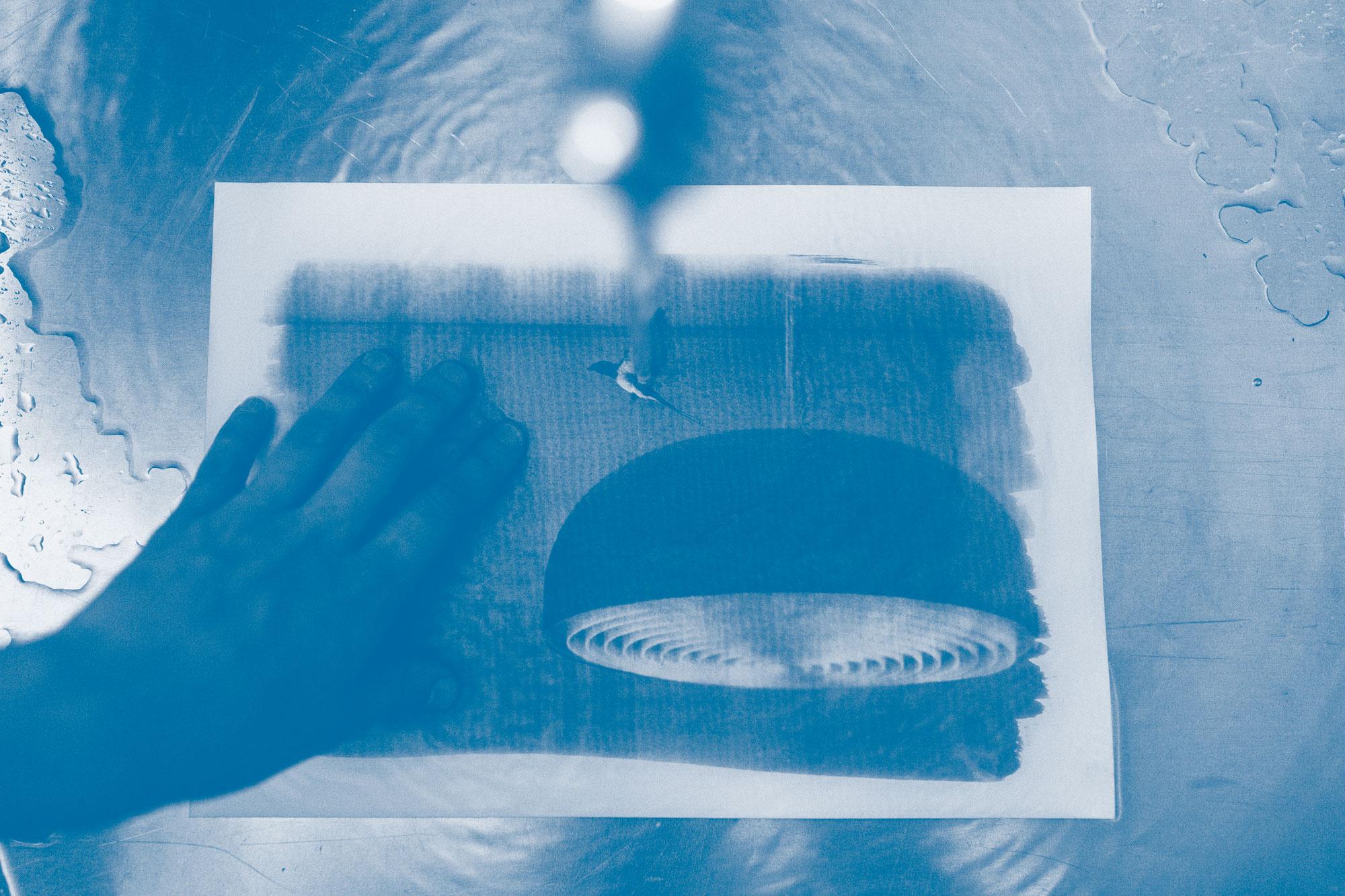 Cyanotypie Druck wird ausgewaschen. Mit Licht und Foto-Chemie malen. Workshop mit Martin Schachenhofer in der Guten Stube Andelsbuch.